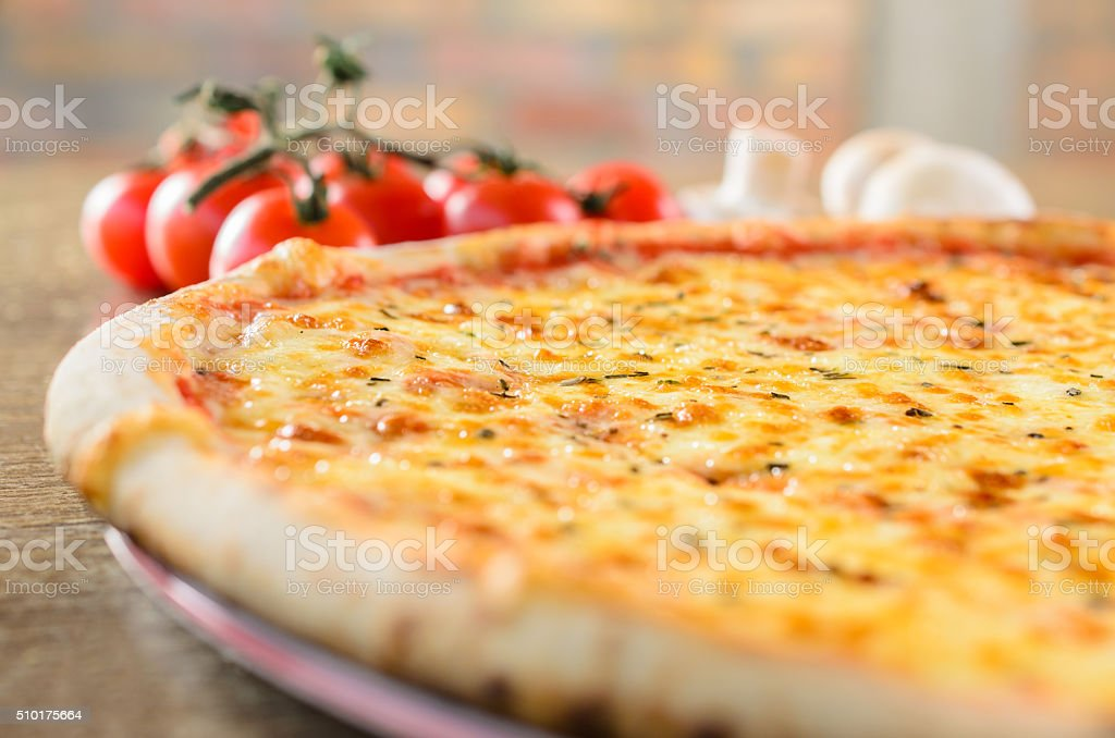 Pizza with cherry tomato and mushrooms in the background stock photo