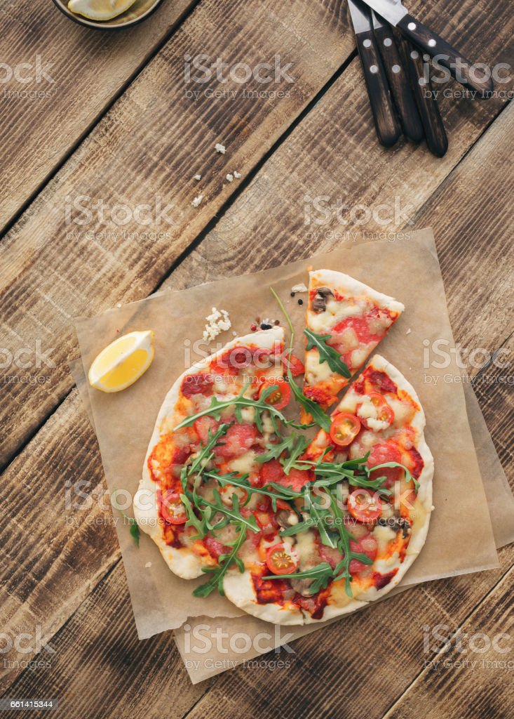 Pizza with melting cheese and sausage salami, mushrooms, tomatoes on rustic wooden table stock photo