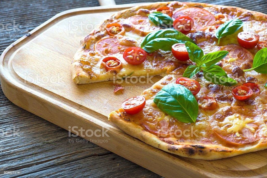 Pizza with mozzarella, tomato and basil leaves stock photo