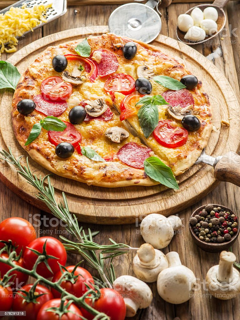 Pizza with mushrooms, salami and tomatoes. stock photo