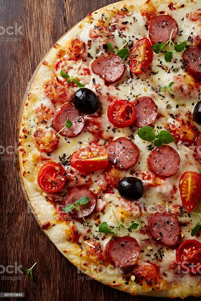 Pizza with pepperoni and cherry tomatoes stock photo