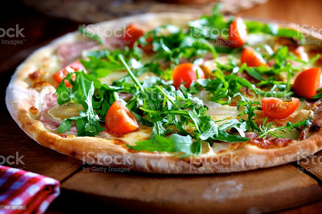 Pizza with rocket salad, ham and cherry tomatoes stock photo