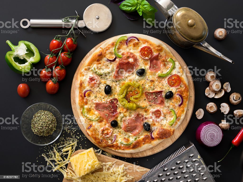 Pizza with tomatoes, cheese, basil and ham stock photo