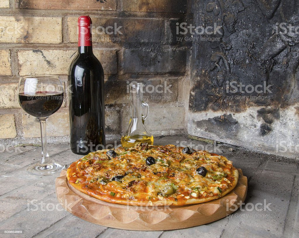 Pizza with wine and oil on a firebricks background stock photo