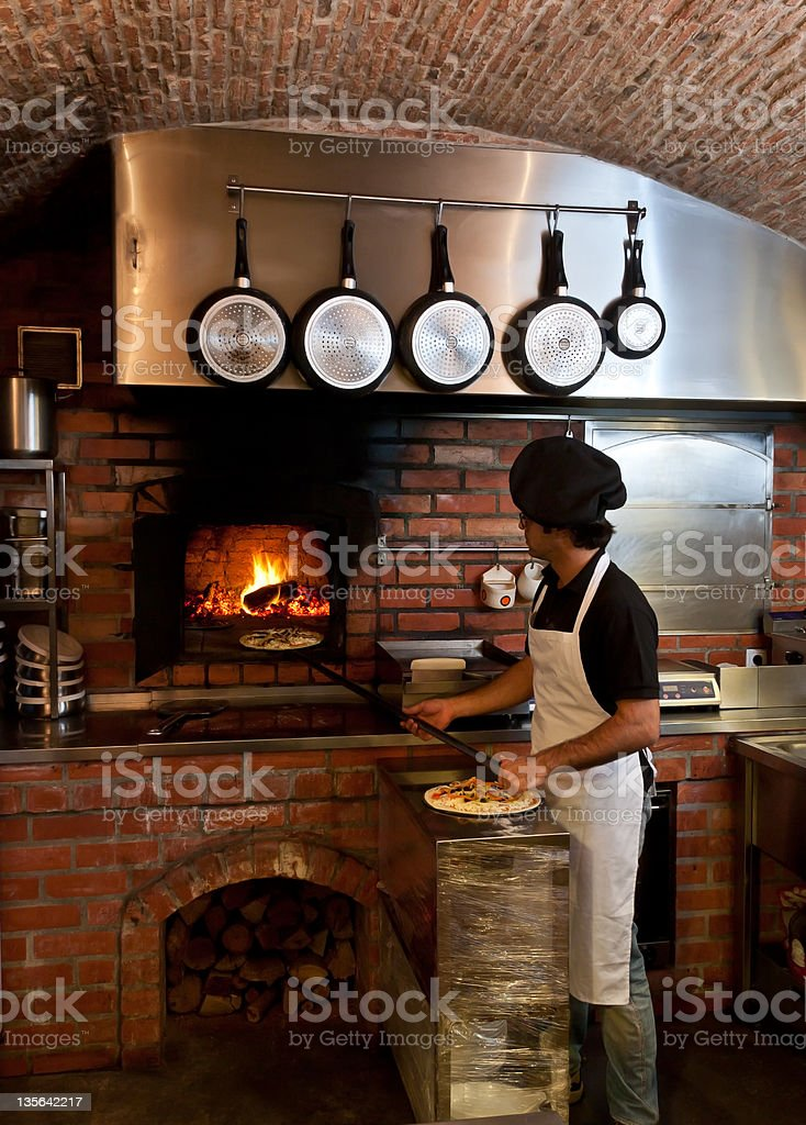 Pizzeria Chef put the pizza inside Wood Oven stock photo
