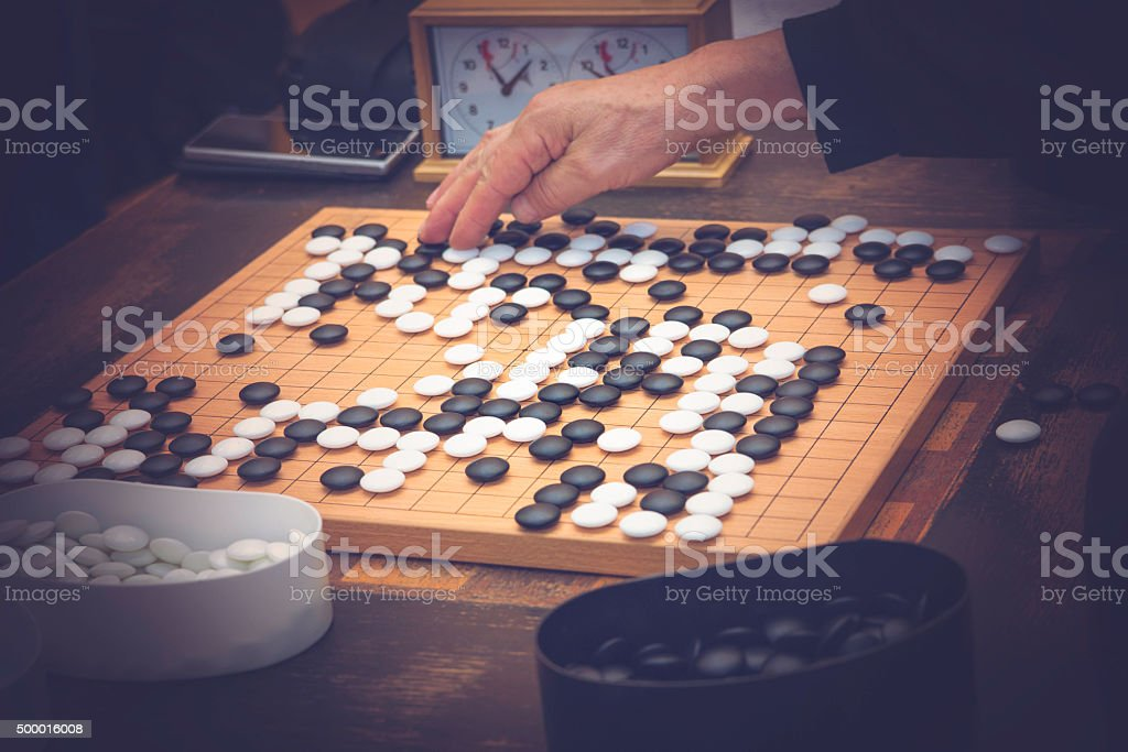 Place a Go stone in a game stock photo