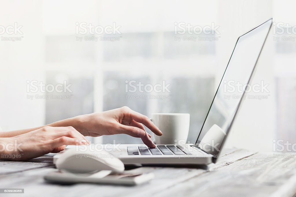 Place of work. Hands on laptop keyboard stock photo