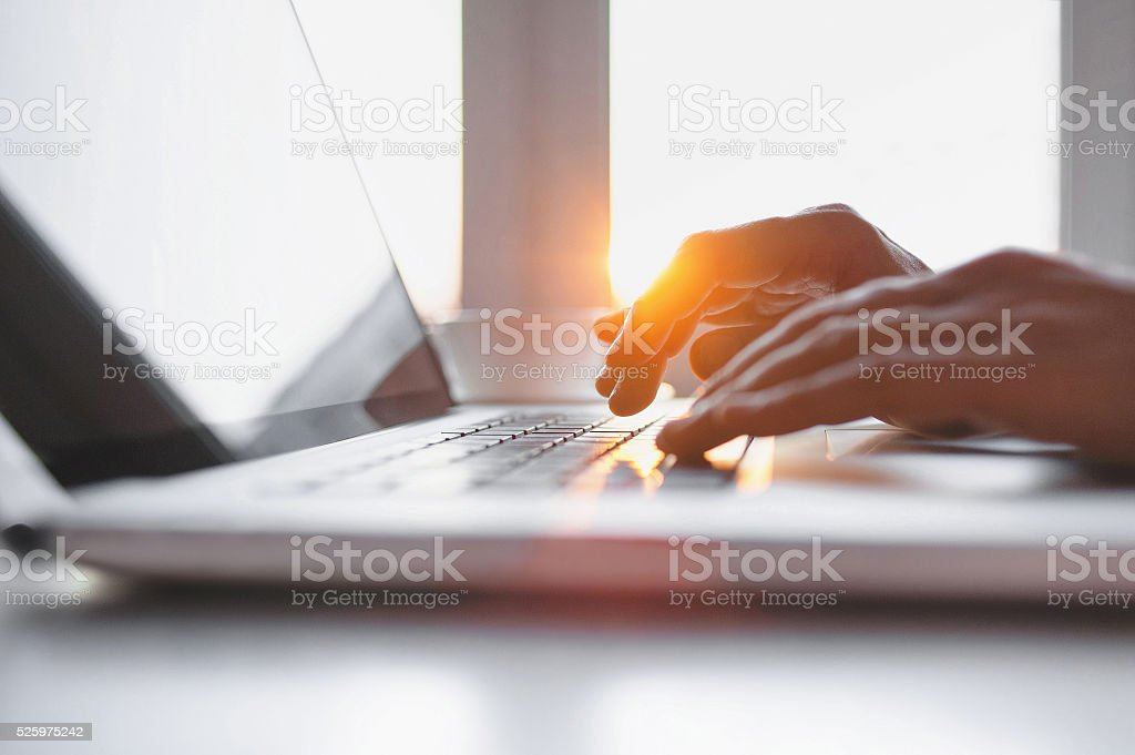 Close-up of male hands typing on laptop keyboard