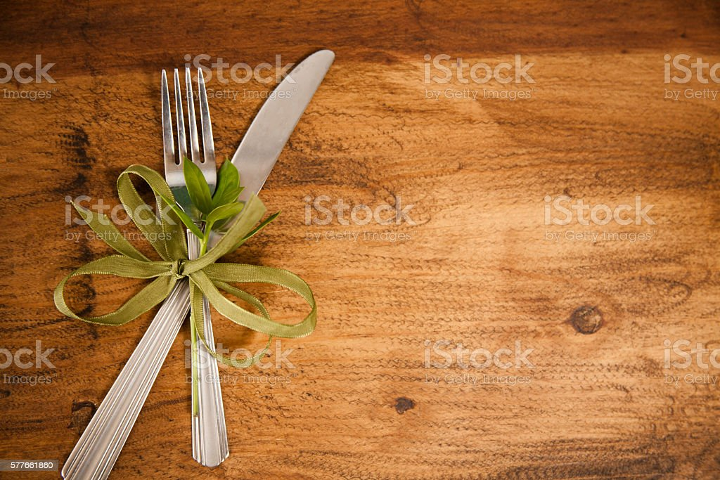 Place setting on wooden table.  Silverware with green bow. stock photo