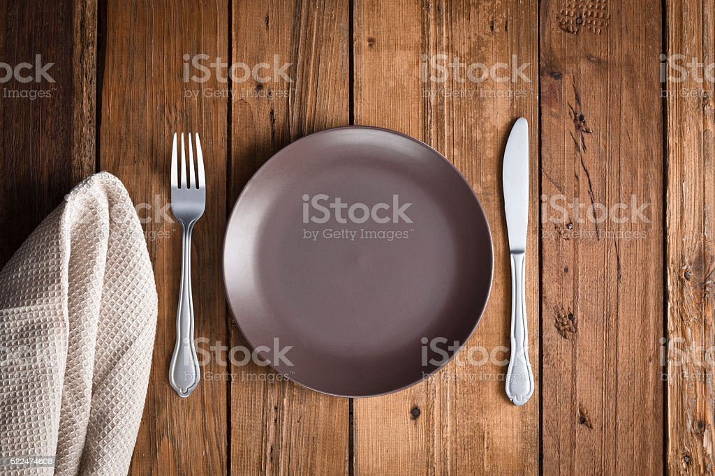 Top view of a place setting on dark table. Predominant color is...
