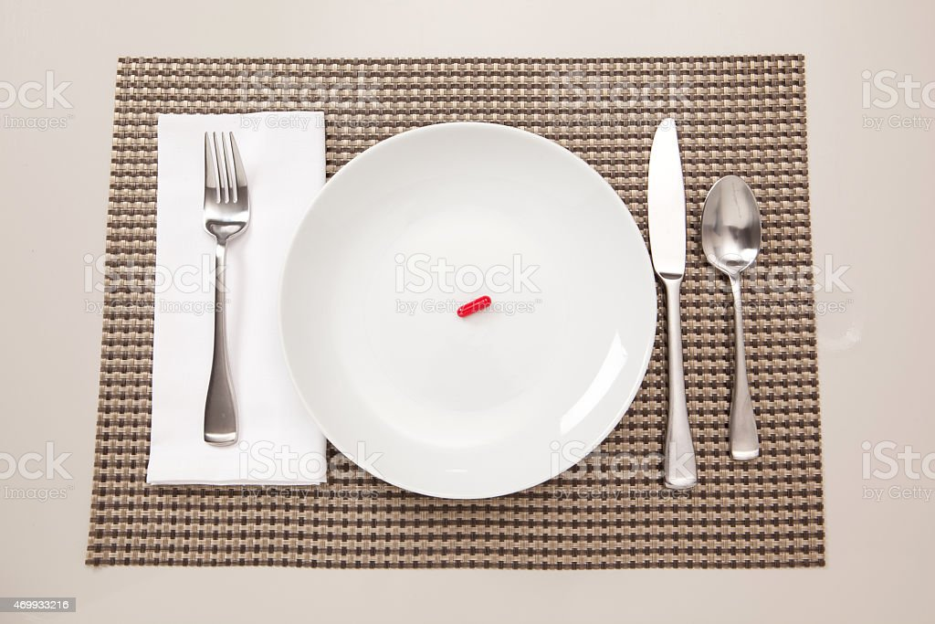 Place setting with a single red pill on it. stock photo