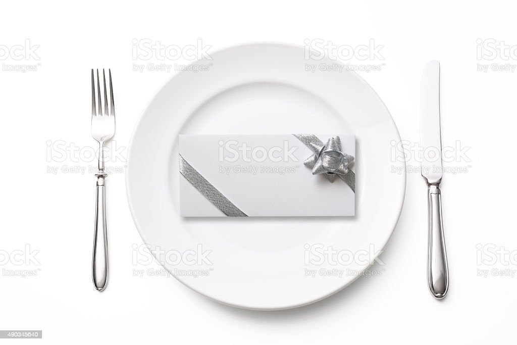Place setting with blank envelope on white background stock photo