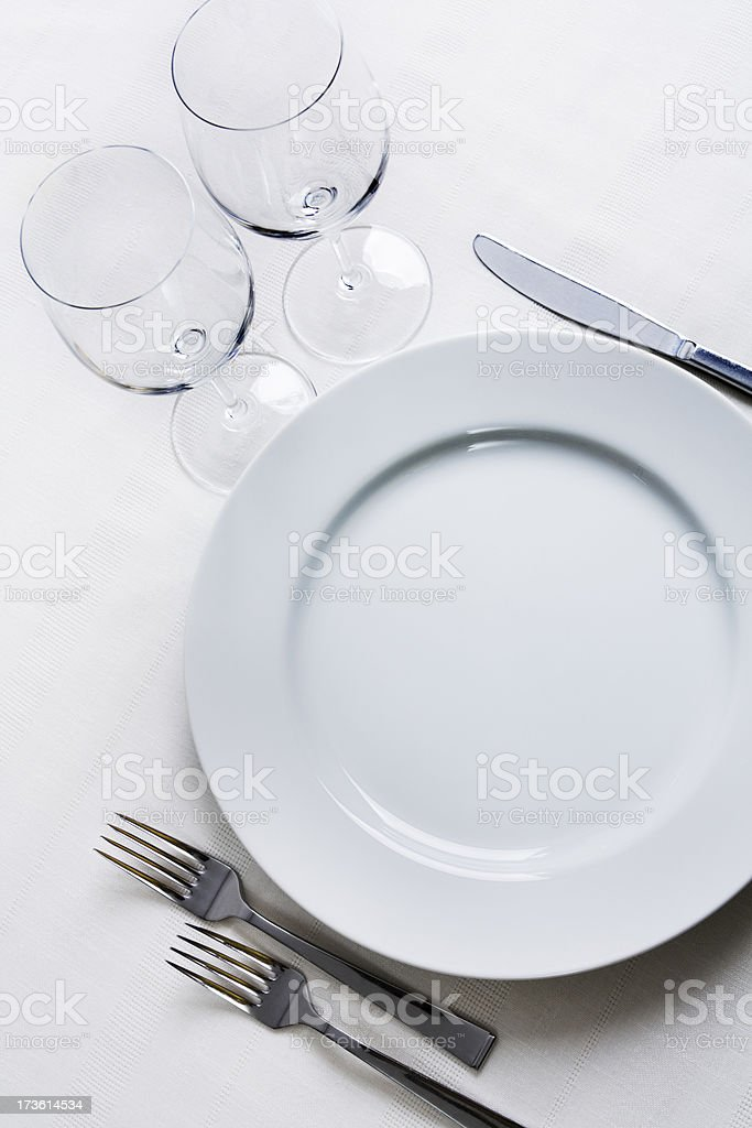 Place Setting with Plate, Silverware, Wine Glasses on White Tablecloth stock photo