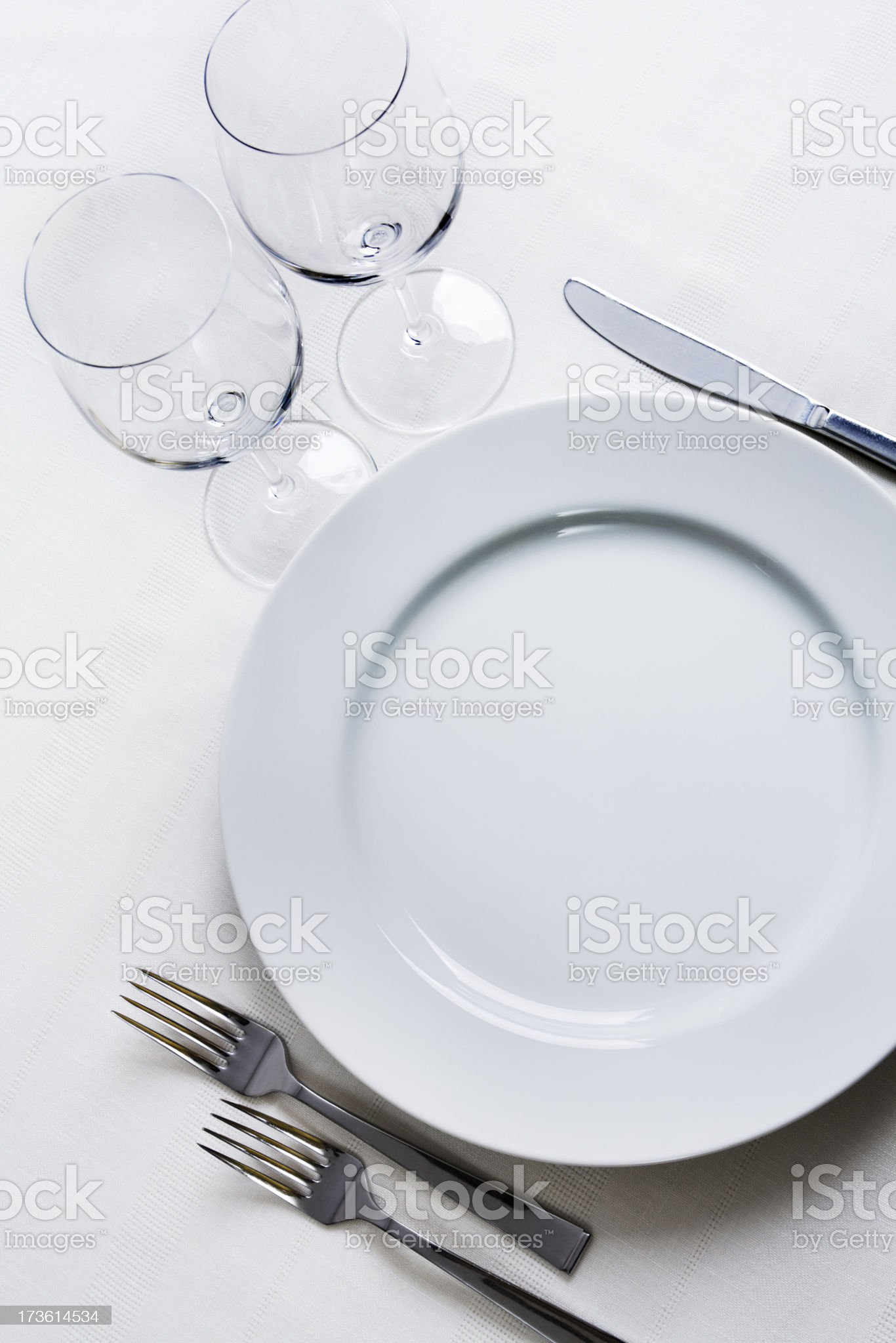 Place Setting with Plate, Silverware, Wine Glasses on White Tablecloth royalty-free stock photo