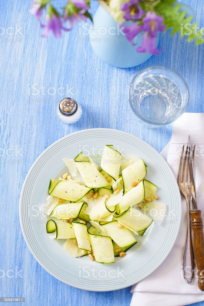 Place setting with zucchini carpaccio, water and flowers stock photo