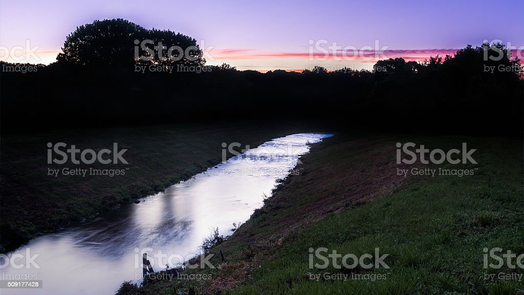 Placid Stream under Purple Sunset stock photo