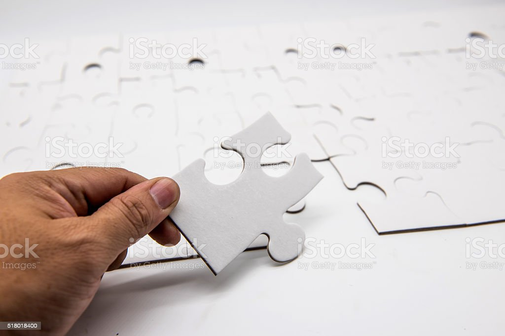 Placing missing a piece of puzzle stock photo