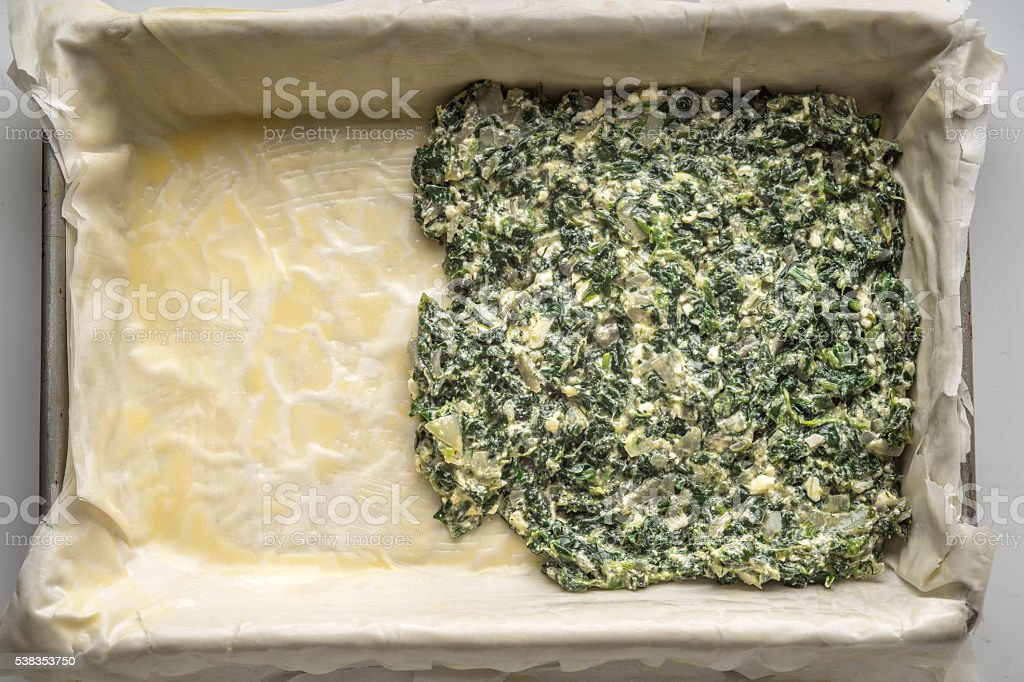 Placing the filling for spanakopita on the dough stock photo