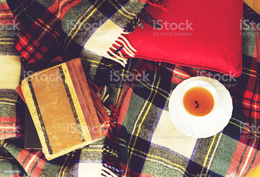 Plaid, cup of tea, books on wooden background. Top view. stock photo
