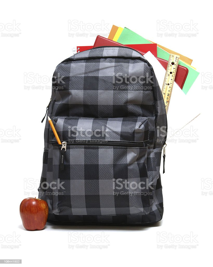 A plaid school backpack with supplies and apple royalty-free stock photo