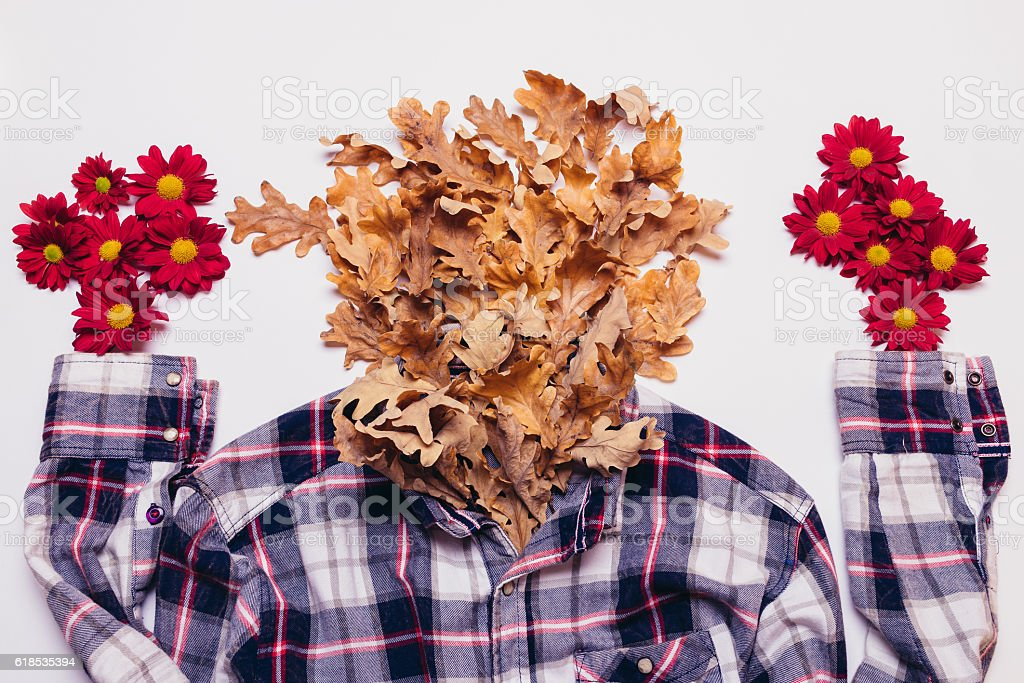 Plaid shirt with dry leaves and red flowers stock photo