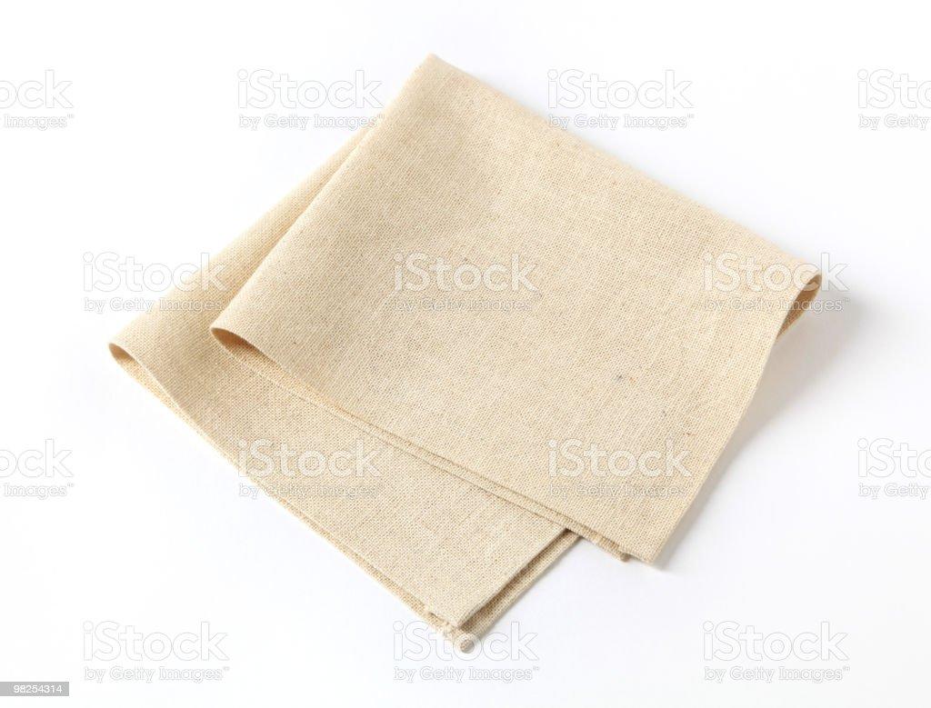 A plain beige fabric napkin folded in half stock photo