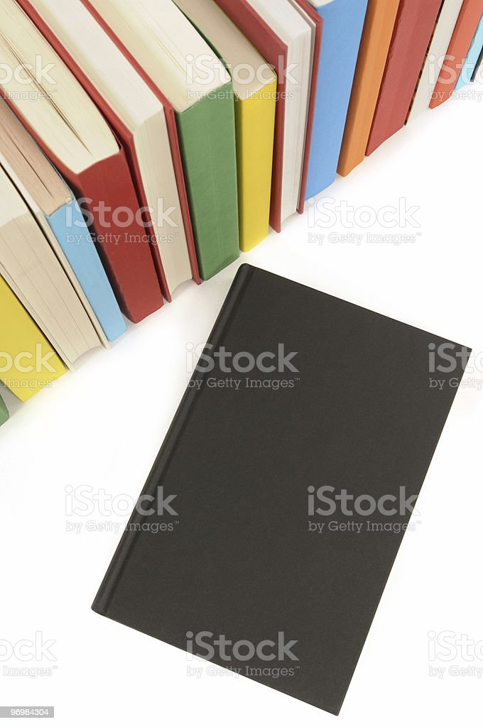 Plain black book with row of colorful books stock photo