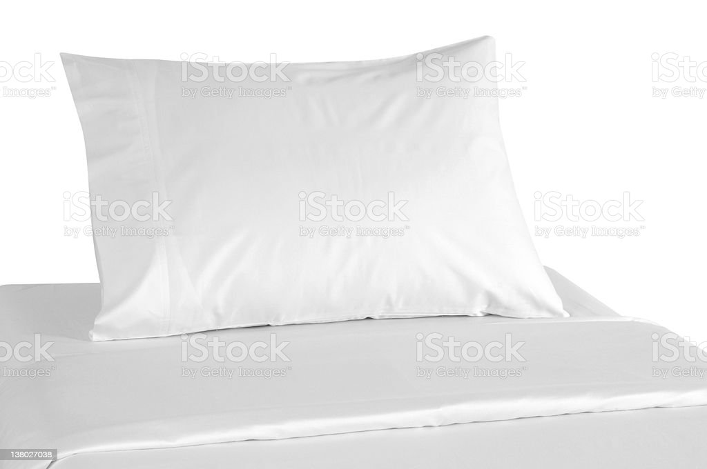 Plain white bedding covering a pillow and a bed stock photo