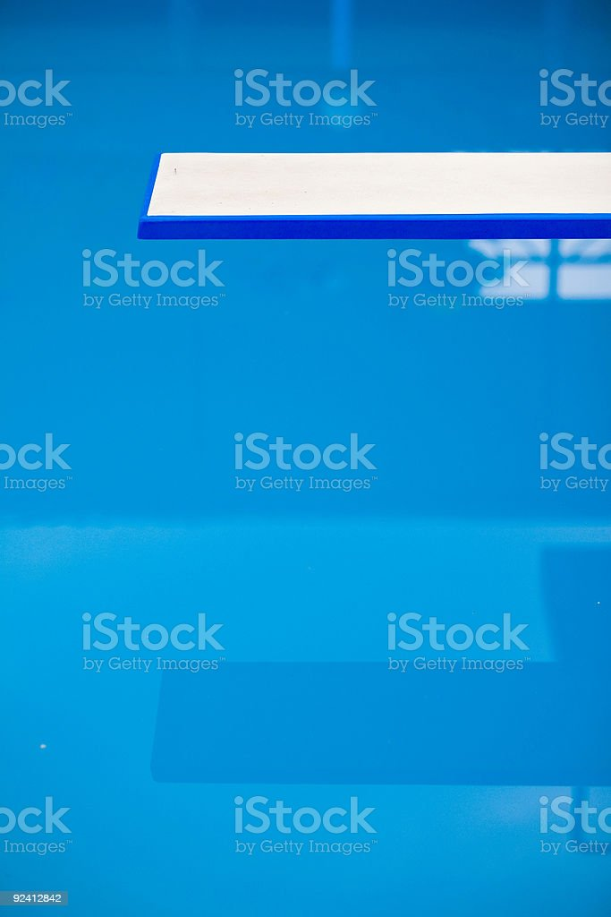 Plain white diving board over a blue swimming pool stock photo
