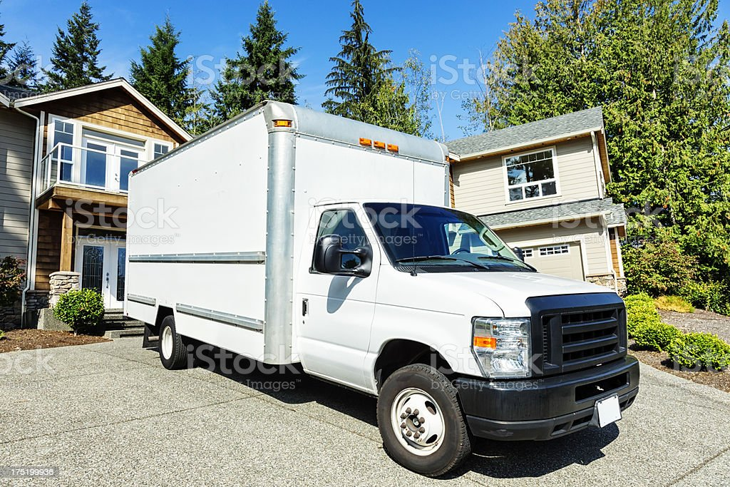 Plain White Moving Truck in Driveway stock photo