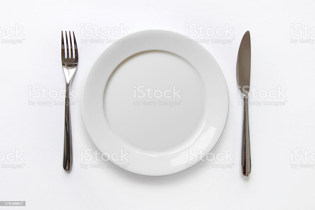 Plain white plate with fork and knife on white background stock photo