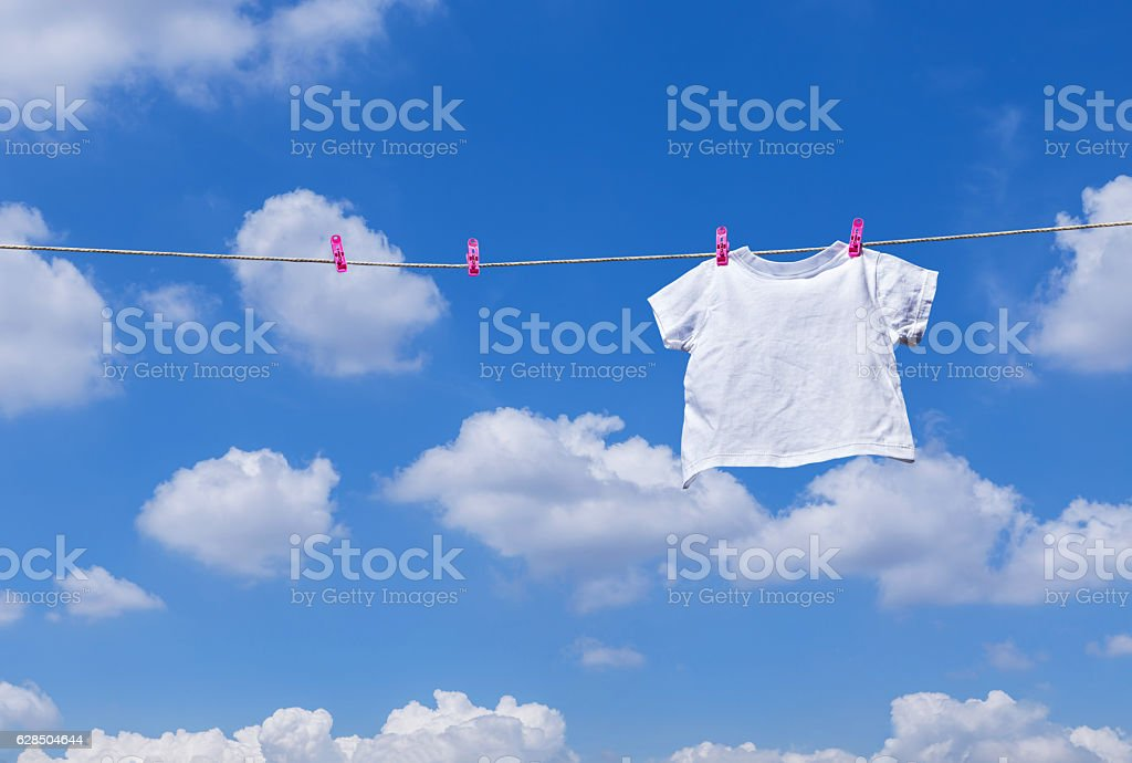 plain white T- shirt hanging on clothes line stock photo