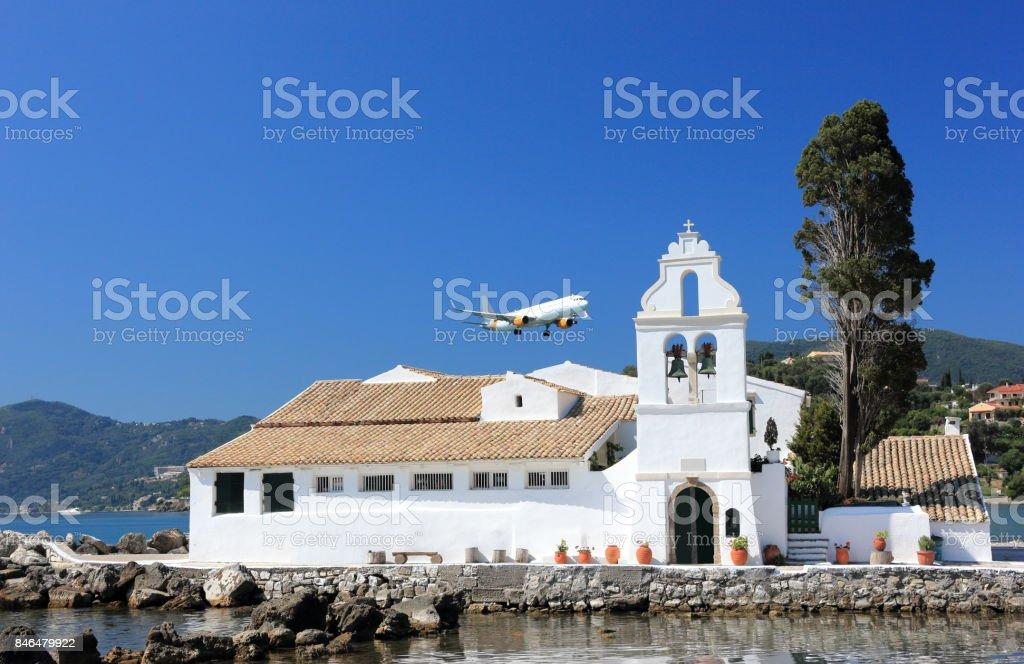 Plane approaching Corfu airport over Vlacherna monastery. Kanoni peninsula,  Corfu island, Ionian Sea, Greece. stock photo