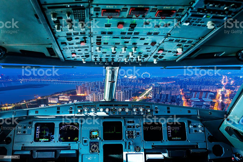 plane cockpit and city of night stock photo