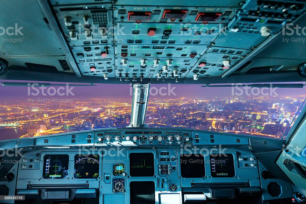 plane cockpit and the city of night stock photo