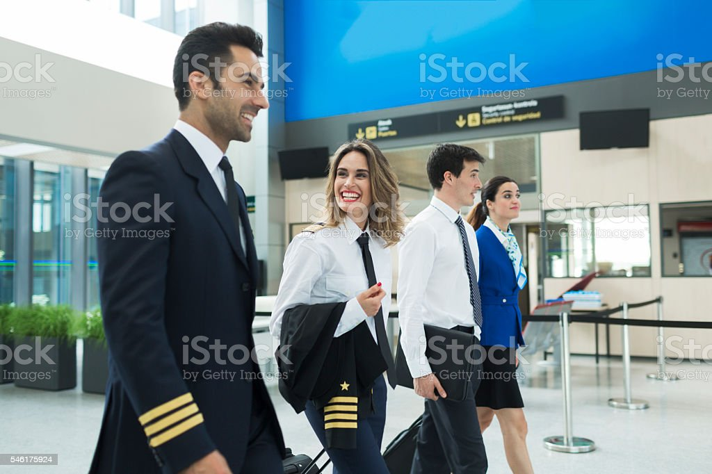 Plane crew walking in airport terminal near airline office. stock photo