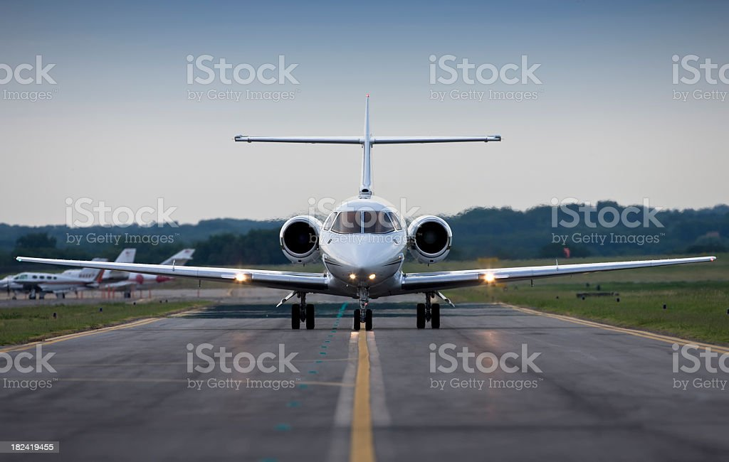 Plane departing on the runway at dusk stock photo
