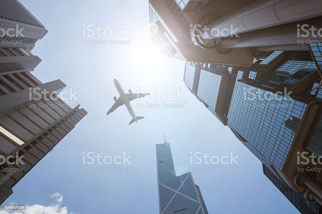 Plane fly on Business towers in HongKong stock photo