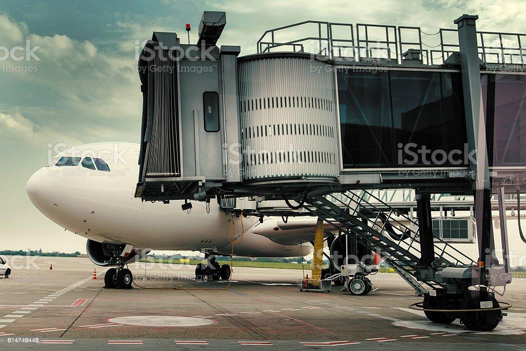 Plane in airport near jet bridge stock photo