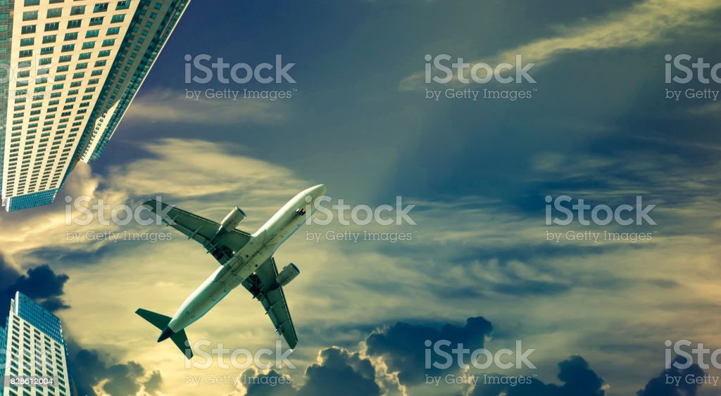 plane in sky on skyscrapers background stock photo