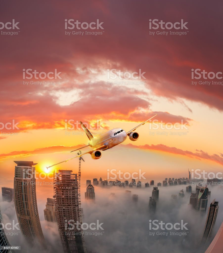 Plane is flying over Dubai against colorful sunset in United Arab Emirates stock photo