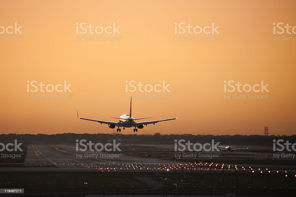 Plane landing at airport against an orange sky stock photo