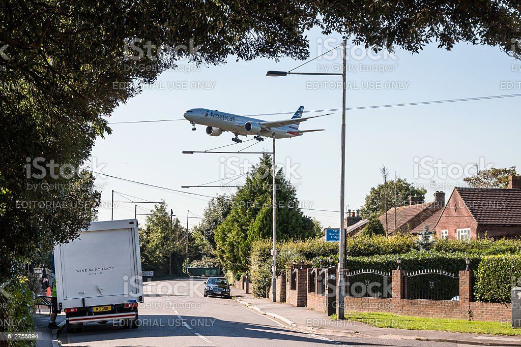 Plane low approach above houses stock photo