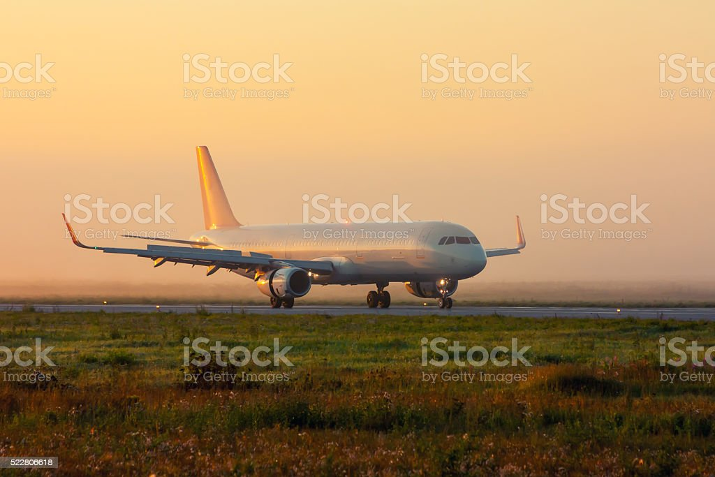 Plane on the taxiway in the early foggy morning royalty-free stock photo