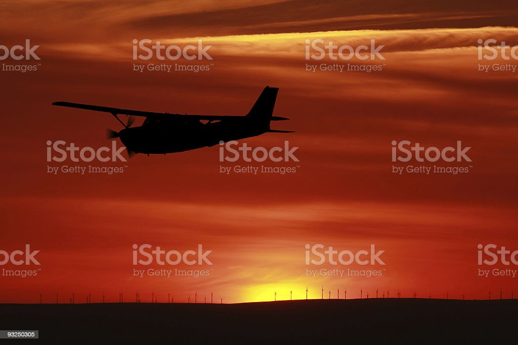 Plane silhouette flying in sky behind a vibrant sunset stock photo