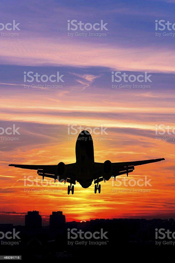 Plane taking off during sunset stock photo
