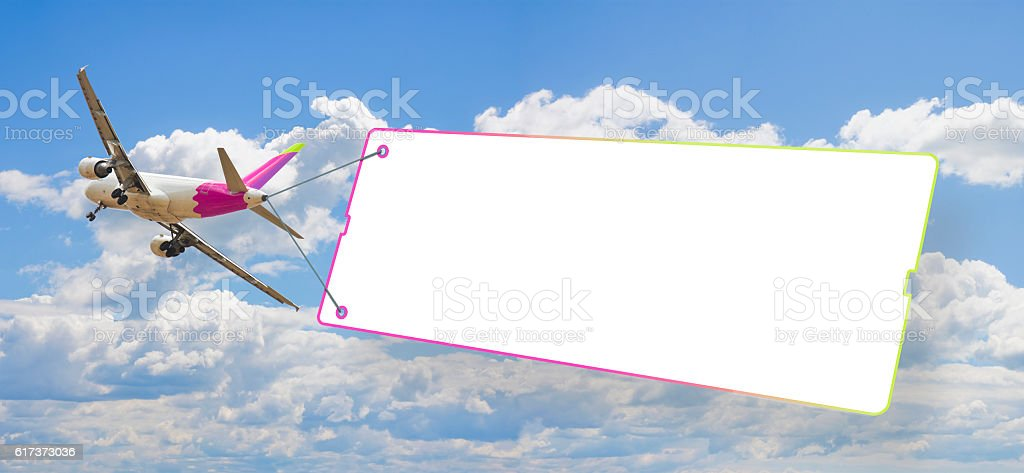 Plane towing a blank signboard against a blue sky stock photo