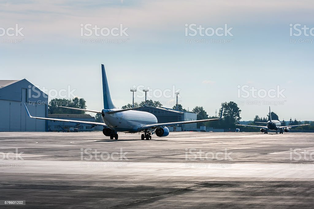 Planes taxiing one after another in backlit royalty-free stock photo