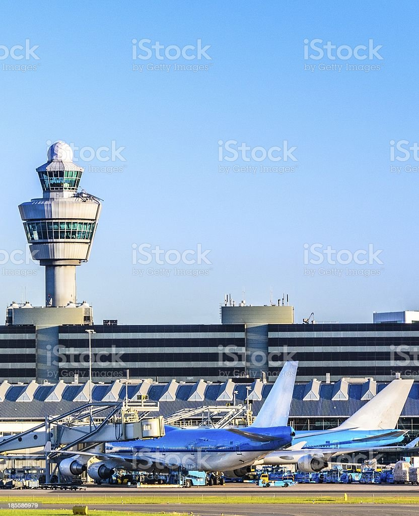 Planes waiting at a terminal in an airport stock photo