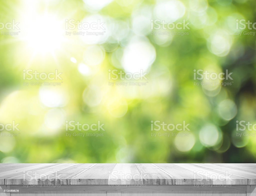 plank white wood table top with blur green tree bokeh stock photo